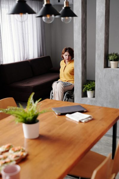 woman using a wheelchair at home in her dining area