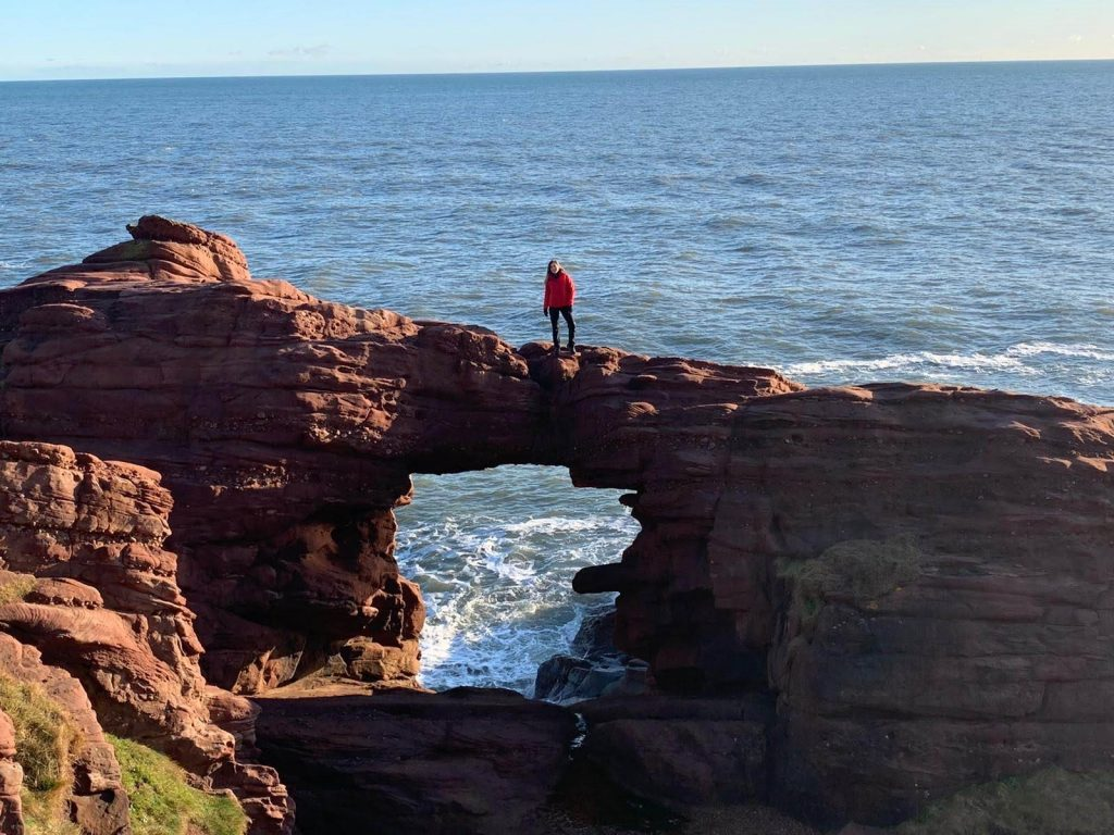 Woman in a red jacket standing on a red cliff with a large opening with the North Sea in the background at Arbroath Cliffs.