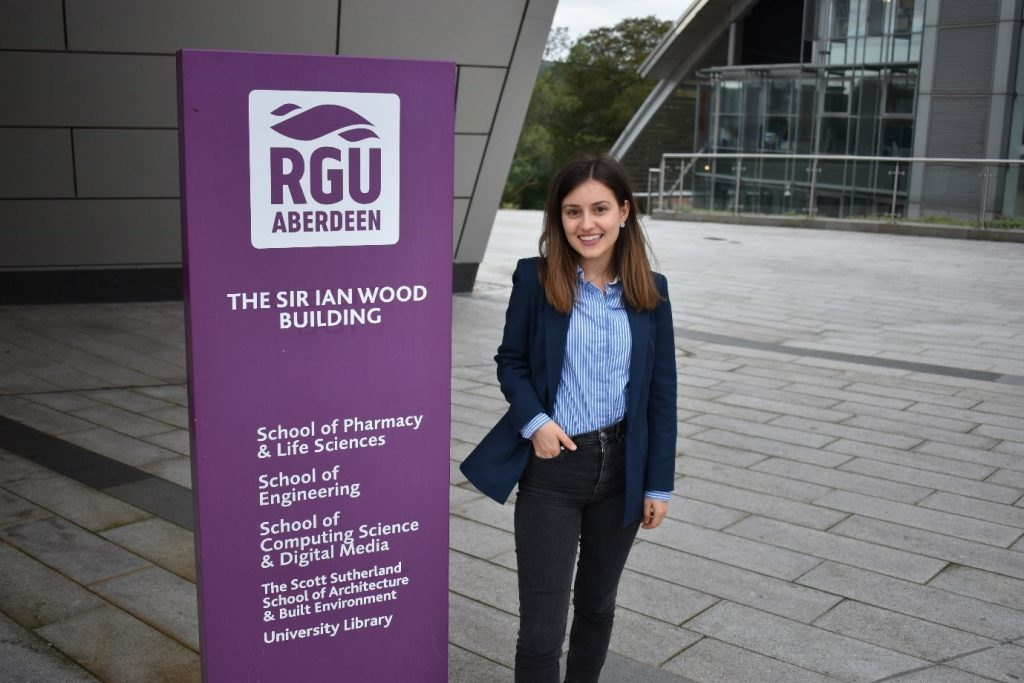 Young woman Data Science student standing next to Robert Gordon University School of Computing sign on the university campus in Aberdeen, Scotland.